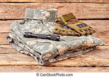 Neatly folded military camouflage clothes with gloves and torch.