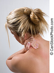Neck And Back Pain - A young adult woman rubs her shoulders...