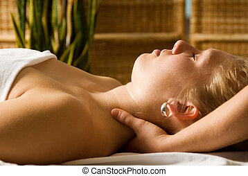 Neck massage - woman in a day spa getting a neck massage by...