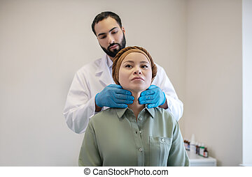 Male doctor in blue gloves examining neck nodes of his female patient