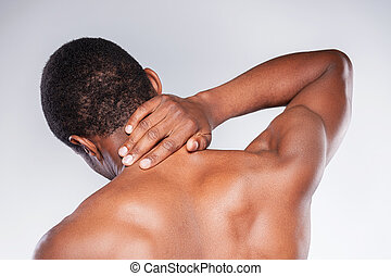 Neck pain. Rear view of young shirtless African man touching his neck while standing against grey background