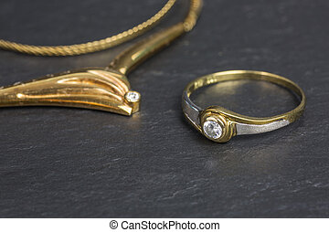 golden necklace with diamond and silver and golden ring with zirconia