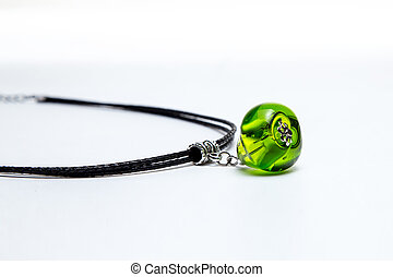Necklace with green glass bead on white background