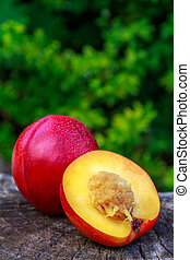 Cut in half nectarine lying on a wooden trunk.