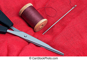 needle and thread on a red background