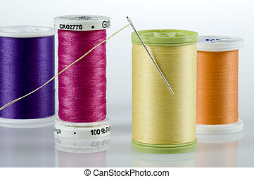 Threaded needle stuck in yellow spool, surrounded by purple, pink and orange spools of thread.
