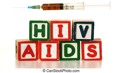 Needle falling on blocks spelling AIDS and HIV in slow...