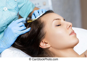 Needle mesotherapy. Cosmetic been injected in woman's head. Thrust to strengthen hair and their growth