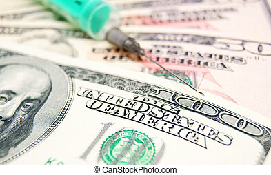 Needle, syringe on money.