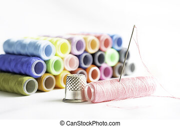 Needle, thimble and colorful spools of thread