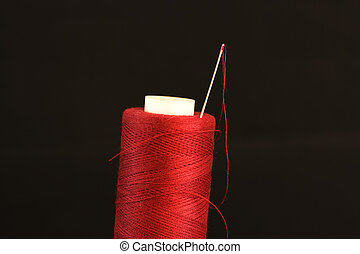 needle with a red thread on a black