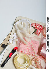 Needlework accessories. Dried flowers and ribbons for crafts. Tools for creativity. On a white tabletop.