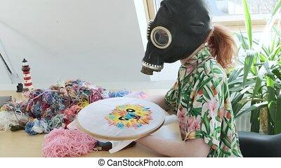 needlework, handicraft in gas mask. Stay home, quarantine ...