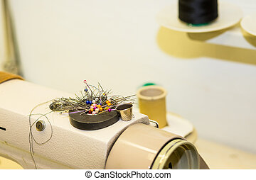 needlework, quilting, sewing and tailoring concept - colorful pins on magnet on sewing machine, tools closeup, thread spools, selective focus, copy space. Work table of a tailor. designer atelier, tailoring process concept