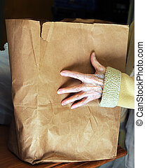 Needy Hands at Food Pantry - Old woman receives paper sack...