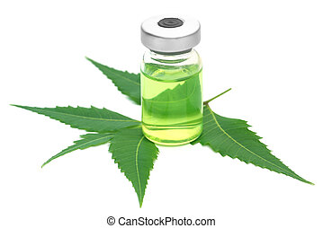 Neem leaves with vial extracted medicine over white...