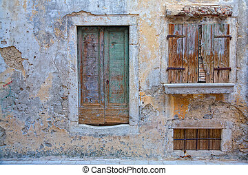 Fragment of an old house in Scradin, Croatia with a door and two windows