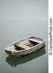 Single worn old rowing boat on calm sea