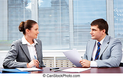 Photo of confident business partners looking at each other during formal communication
