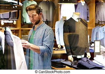 negozio, comprare, giovane guardare, uomo, vestiti
