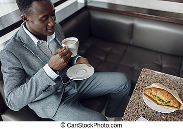 Negro businessman having lunch in office cafe