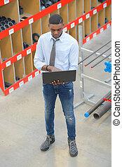 negro, director, con, computador portatil, en, almacén