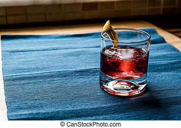 Negroni Cocktail with lemon peel and ice