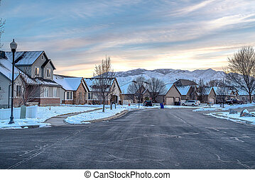 Neighborhood street with road along houses overlooking mountain and cloudy sky