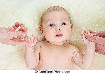 nena, tenencia, paternal, manos, acostado, en, piel, cama