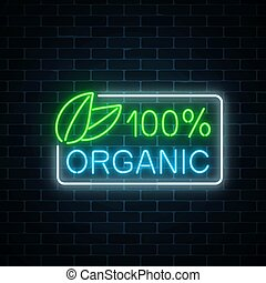 Neon 100 percent organic production sign on dark brick wall...