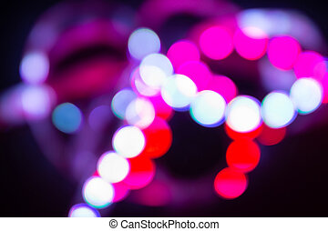 Neon bokeh lights on black. Bright abstract blurred background