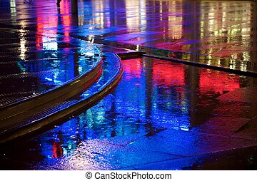 Red and blue neon lights reflected in puddles on the pavement (sidewalk, street)