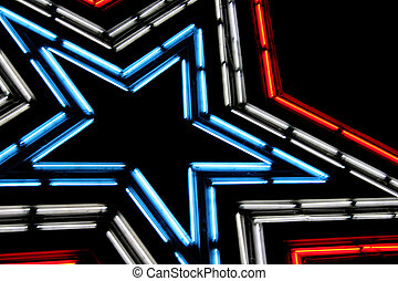 Large neon lit star with patriotic colors of red, white and blue. Shot against the night sky.