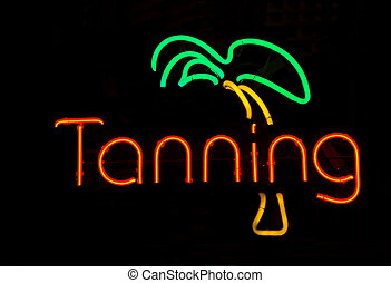 A neon light tanning booth sign in a store window.