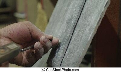 Nepalese craftsman working on traditional Mani slate stone...