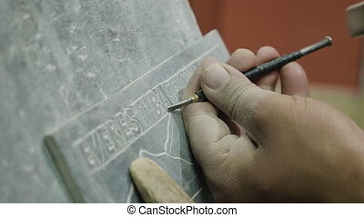 Nepalese craftsman working on traditional Mani slate stone...
