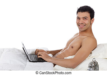 Nepalese young man in bed, laptop