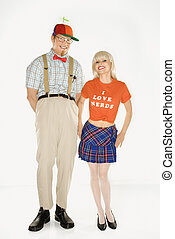 Caucasian young man dressed like nerd wearing propeller hat with Caucasian blonde young woman wearing tshirt reading I love nerds and plaid skirt.
