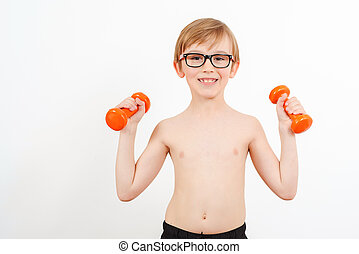 Nerd boy raising a dumbbell. Cute child training with dumbbells, isolated on white.