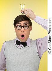 Nerd has an idea. Young nerd man holding a light bulb on his...