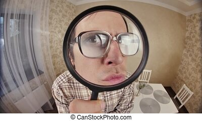 Funny nerd looks through magnifier