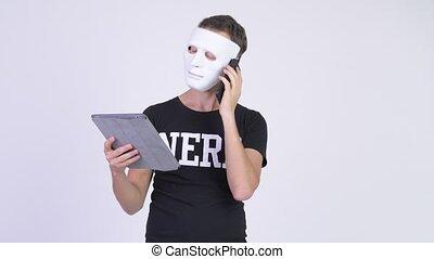 Nerd man as hacker wearing white mask while using phone and...