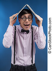 Nerd with book. Young nerd man holding a book on head while...