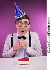 Nerds with cake. Young cheerful nerd man in glasses sitting at the table with a birthday cake on it