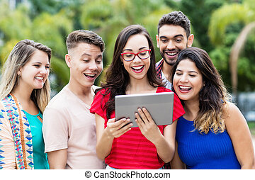 Nerdy french female student with tablet computer and group of international students