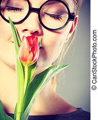 Nerdy girl smelling flower.