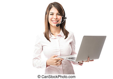 Cute and nerdy young woman with a laptop computer working as a tech support rep in a call center