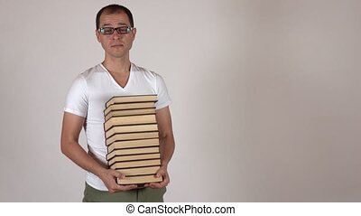 Nerdy man in black rim glasses carrying big stack of books against gray background, isolated. 4K shot