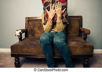 nervioso, joven, sofá, atrás, cojín, paliza, hombre