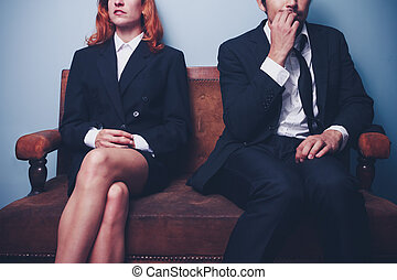 Nervous businessman sitting next to confident businesswoman